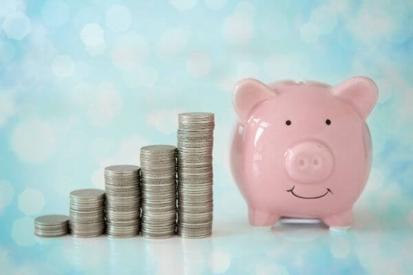 Picture of a saving pig jar and coins to show how can I save $5000 in 3 months.
