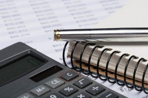 Picture of notebook and calculator while planning how to make money work for you.