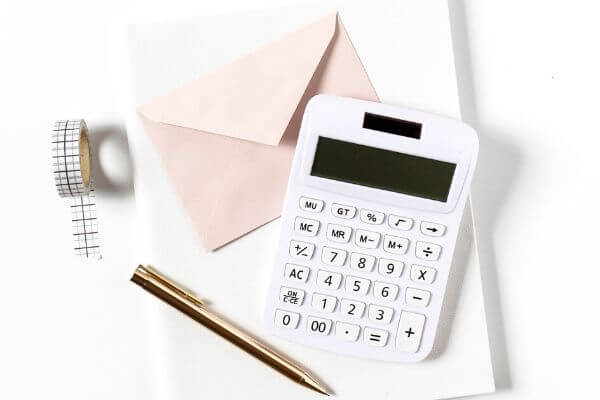 Picture of envelope, paper, and calculator to show How can I save $5,000 in 6 Months with Envelopes?