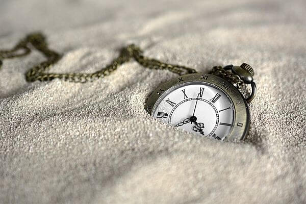 Picture of a clock in sand to represent 30 day financial challenge